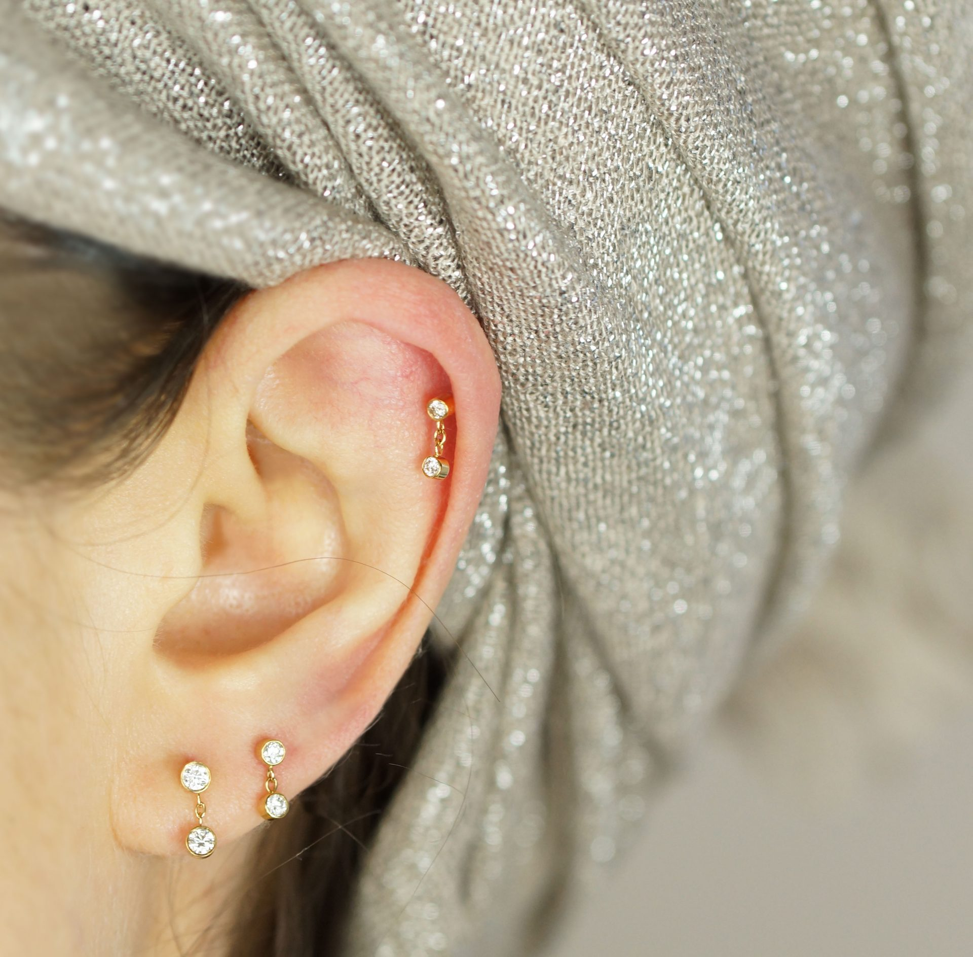 """Create your own """"curated ear"""" with this versatile diamond stud earring. The 18k gold is set with sparkling natural white diamonds. Wear it on the lobe or cartilage to create a personalised ear-style."""