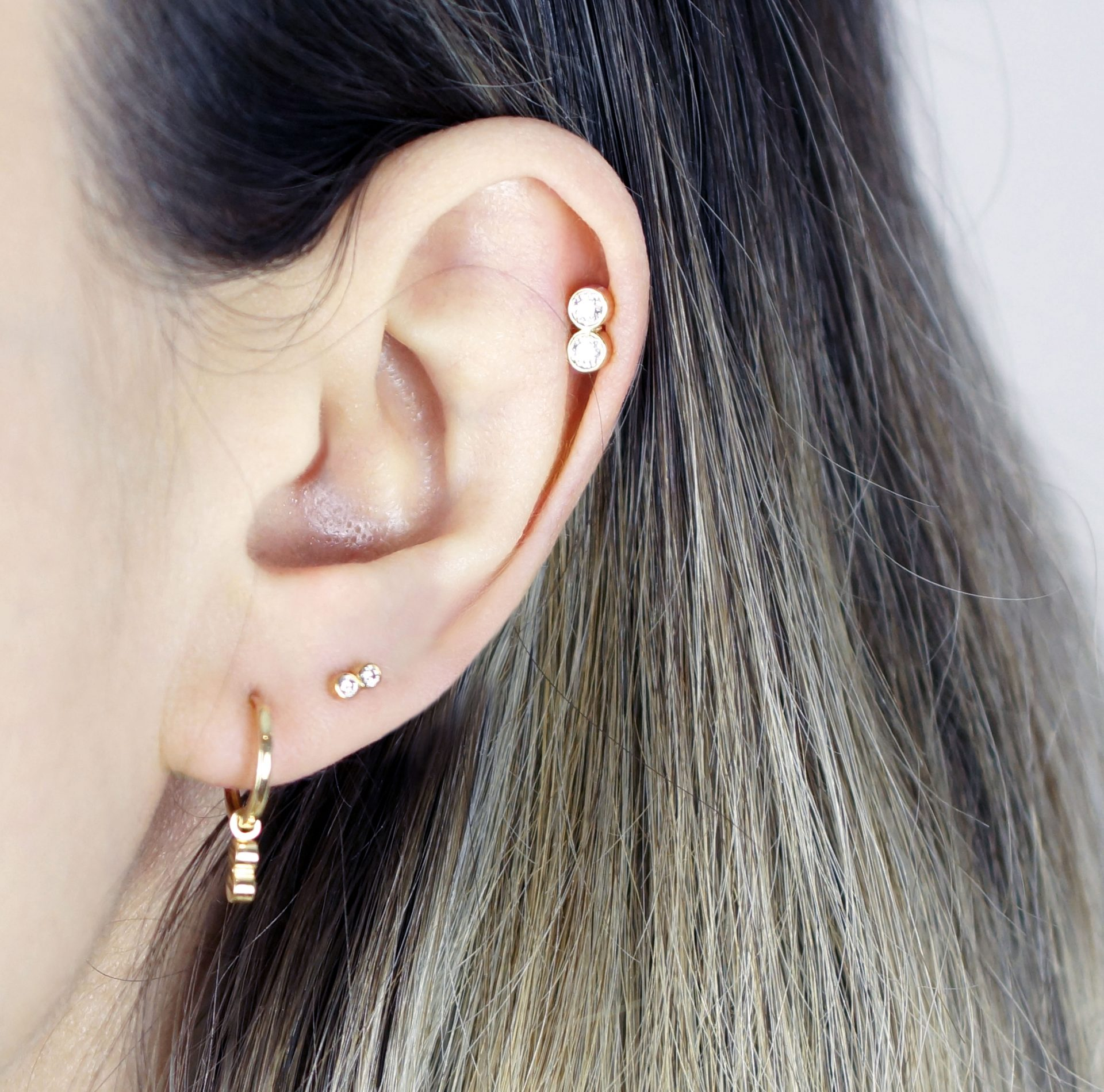 Multiple piercings worn with different types of earrings in an elegant manner is a perfect example of a classy but yet modern ear styling.