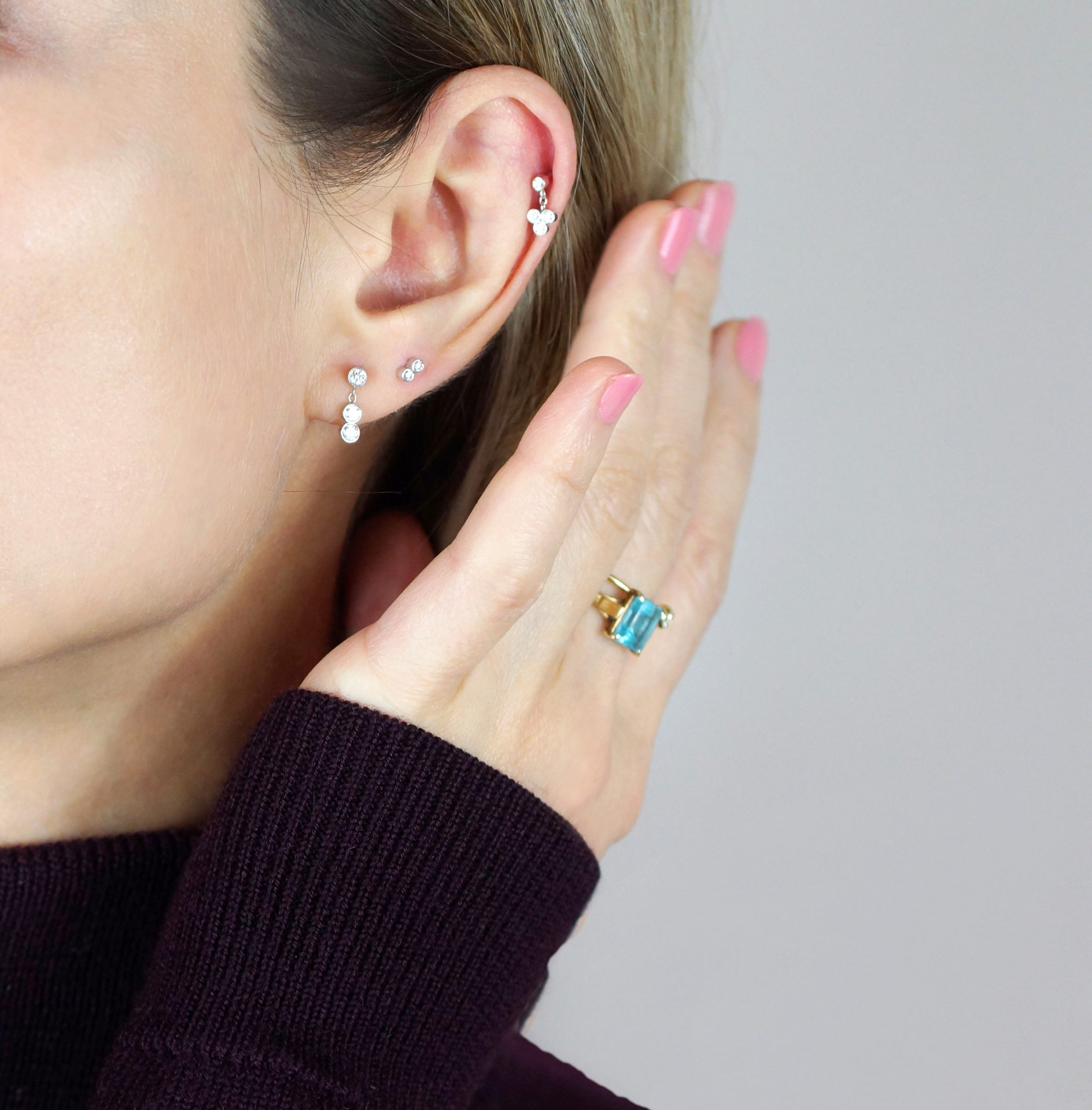 Trendy Types of Ear Piercings and Combinations stacking combos of large diamond studs in simple shapes mixed with hoop stacks or go for a combination of miniature studs along with threader earrings