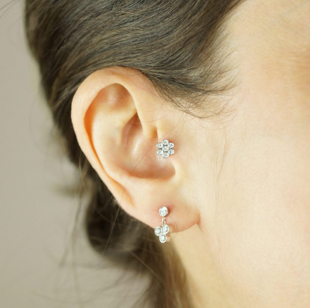"Create your own ""curated ear"" with this versatile Seven Diamonds Flower stud earring. The 18k gold is set with sparkling natural white diamonds. Wear it on the lobe or cartilage to create a personalised ear-style."