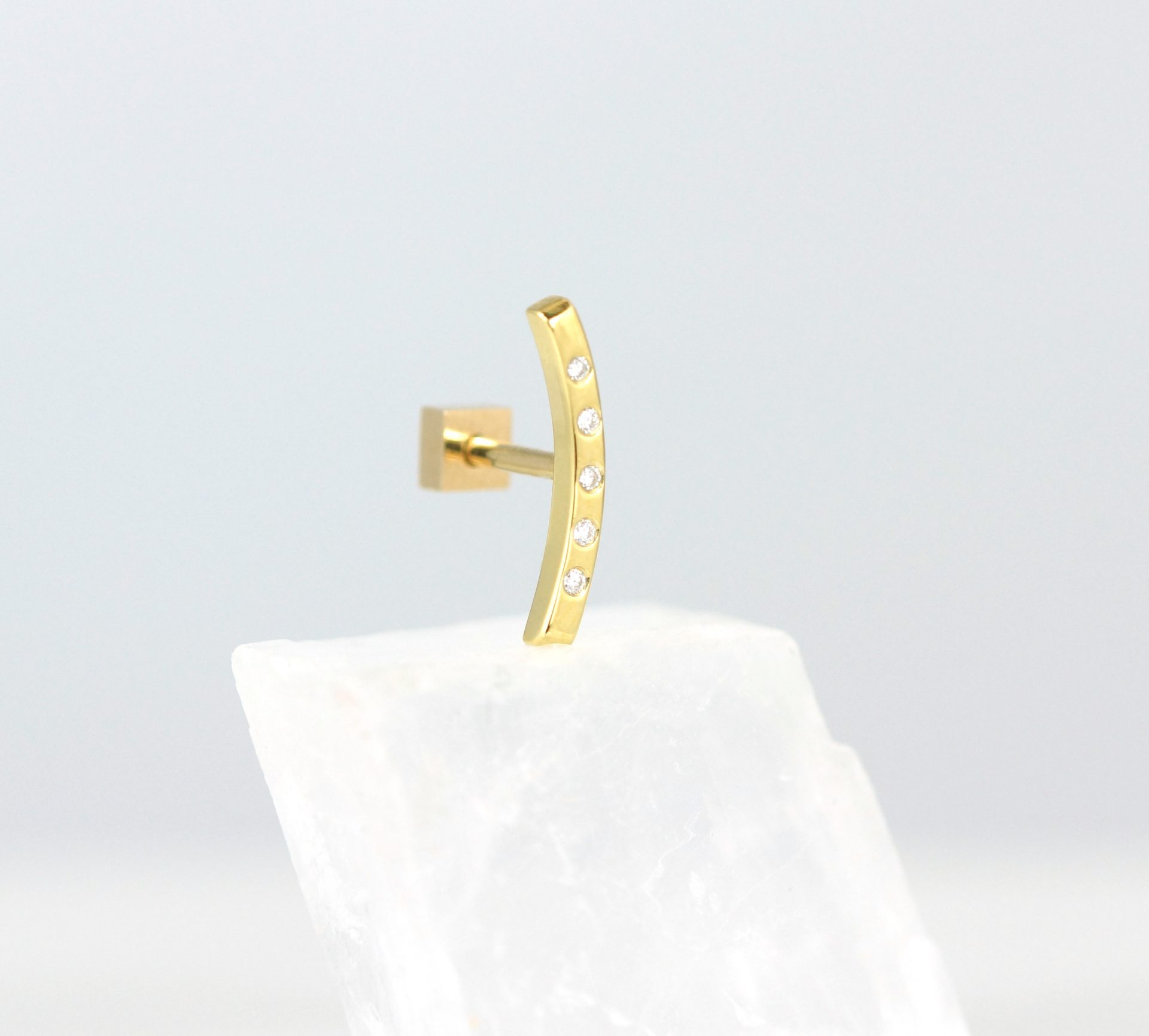 stylish 18k yellow gold curved in a bow shape earring set with five brilliant cut natural diamonds perfectly follows the natural curve of the helix